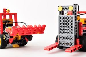 光センサーで黒線やパレットを感知し、モーターやブザーを連動させて荷物を運ぶロボットです。